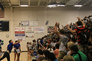 Senior Eric OBrian throws shirts to new students during the welcoming assembly on Aug 30.