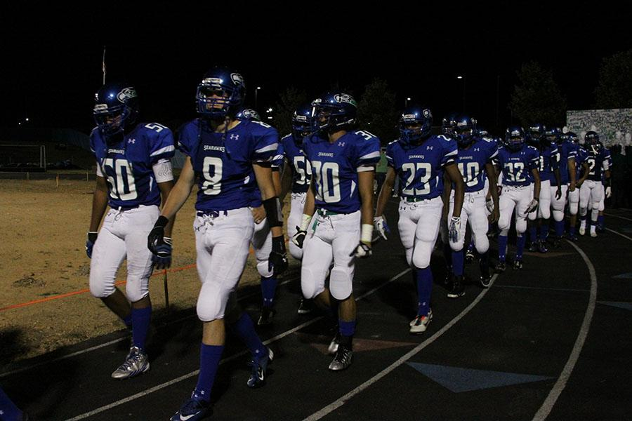 Varsity football walks onto the new turf field for the first time at the Westfield game Sept. 6.