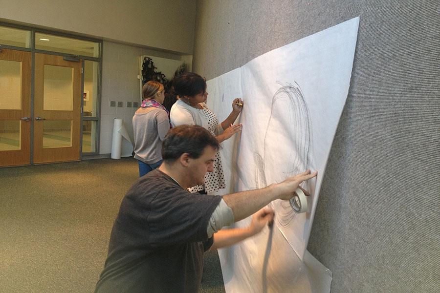 Art teacher Matt Ravenstahl, AFAFA co-founder Ainsley Eakins, and senior Kaitlyn Prisciandaro draw on paper in the art gallery across from the main office as part of the Big Draw campaign. Students are encouraged to add to the wall throughout the month of October.