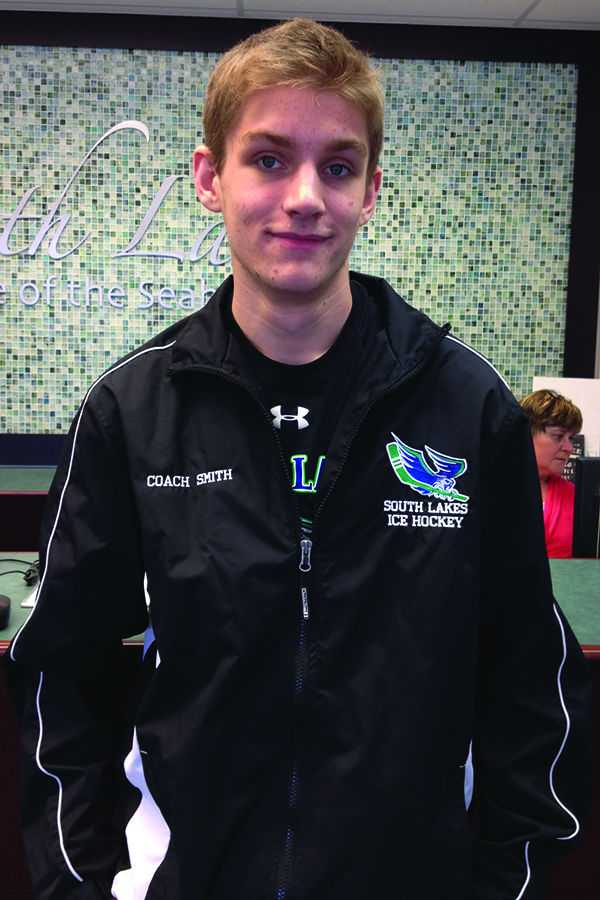 Senior+Spencer+Smith%2C+a+student+ice+hockey+coach%2C+poses+in+his+new+coach+jacket+in+the+front+office.