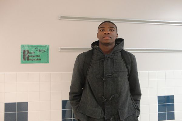Junior combo guard Brandon Kamga poses in the hallway before a morning class.