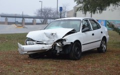 A wrecked car is displayed near the student parking lot as a reminder to students about the dangers of texting while driving.
