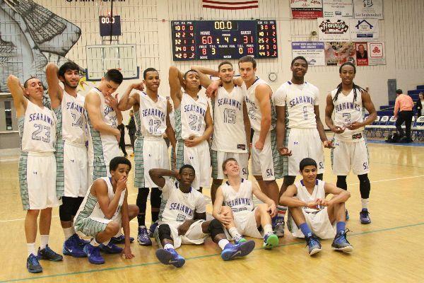 Boys varsity basketball players strike a pose on their home court.