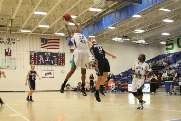 Junior forward Princess Aghayere grabs an offensive rebound in the final seconds of the second quarter during a game against Washington-Lee Jan. 24.  Aghayere posted a double double with 12 points and 12 rebounds in the team's 58-25 win.