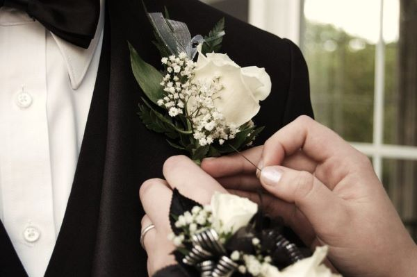 Girl Puts Boutonniere on Her Prom Date, Photo Courtesy of www.www.promdaysecrets.com