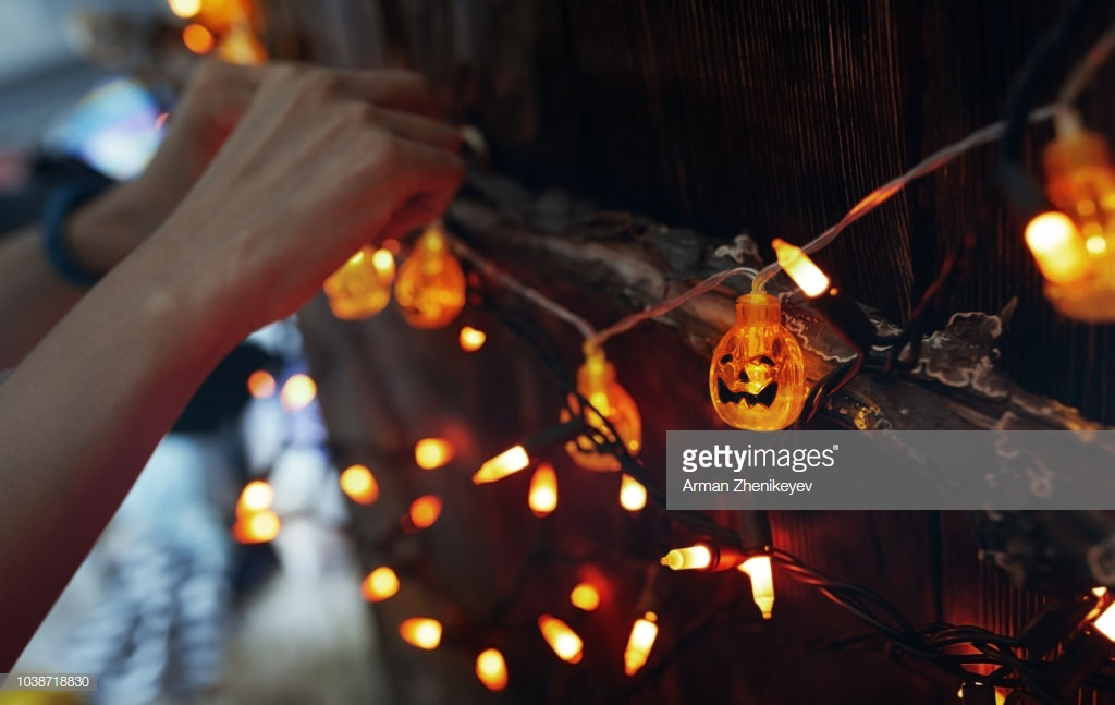 Woman hanging decorative eletric light with pumpkins. Halloween theme. Photo by Arman Zhenikeyev through Getty Images