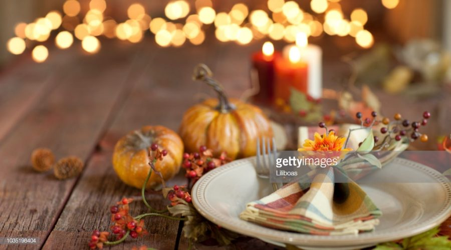 Autumn+Thanksgiving+dining+table+place+setting+on+an+old+rustic+wood+table+with+candles+and+defocused+Christmas+lights