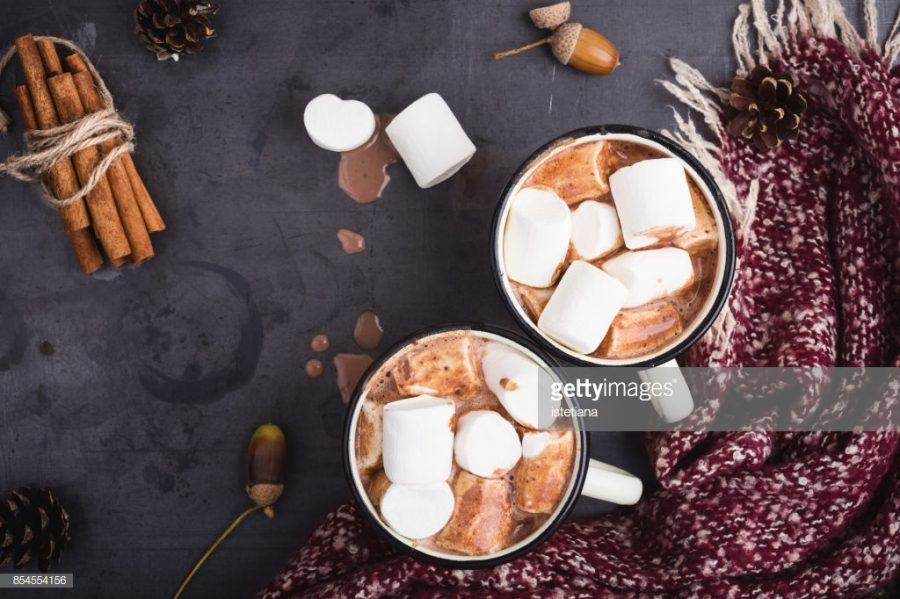 Hot chocolate served in vintage  mugs with marshmallows for two person on table  with woolen scarf wrapped around it; photo taken from Getty Images