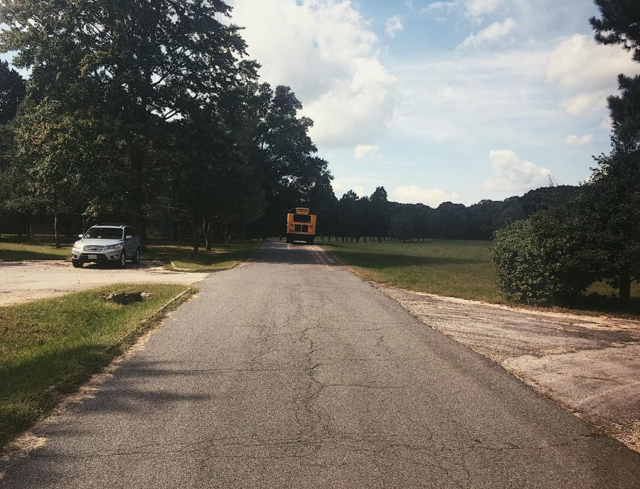 Yellow school bus driving away, referencing recent FCPS decision to shift to