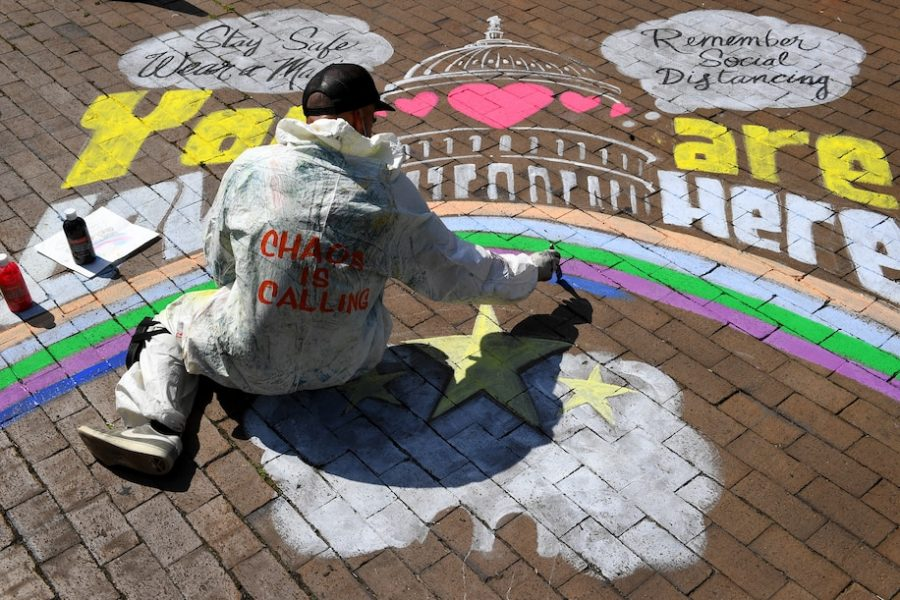 """Local artist Rajan Sedalia works on a mural at Eastern Market Metro Plaza on Tuesday."" - Via Katherine Frey/The Washington Post"